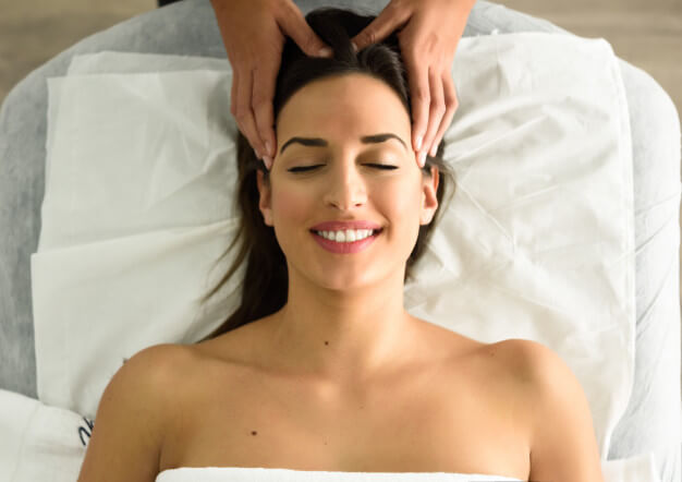 young-smiling-woman-receiving-head-massage